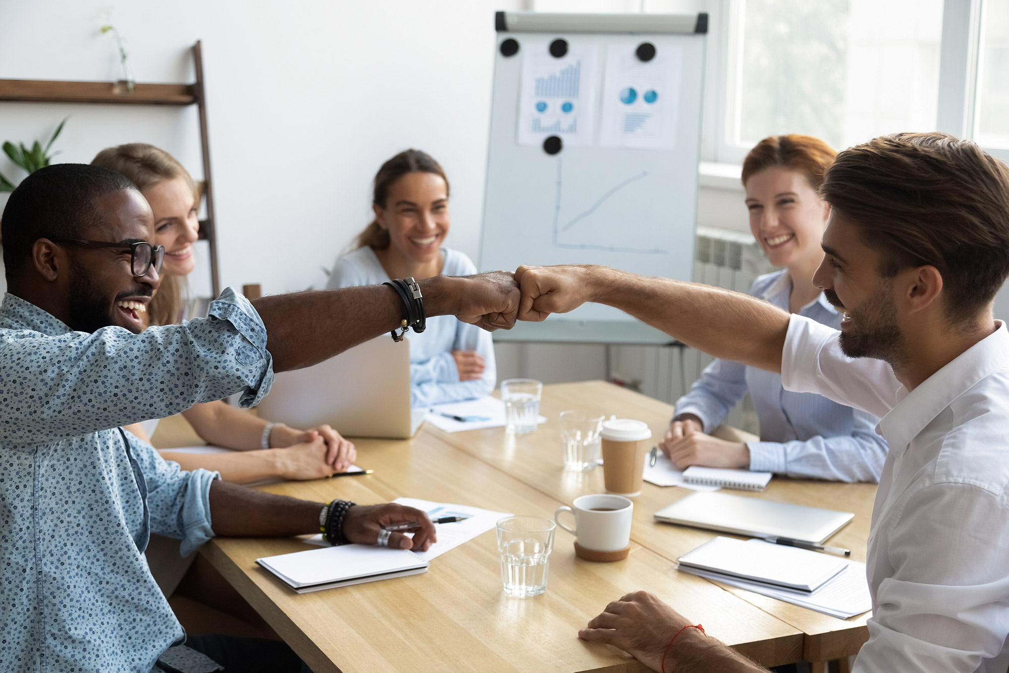 A team of people fist bumping and sitting around a conference table.